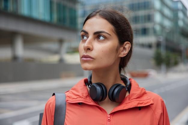 街を歩く女性の歩行者が新しい興味のある場所を発見首の周りにジャケットステレオヘッドフォンを着用してレクリエーション時間を楽しんでいます良い春の日