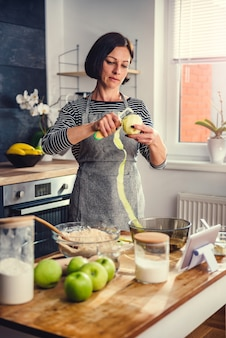 Woman peeling apples in the kitchen