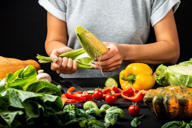 Woman peeling a corn cob, cooking different vegetables. healthy vegetarian food concept.