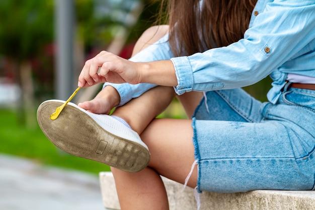Женщина снимает жевательную резинку, прилипшую к ее туфле