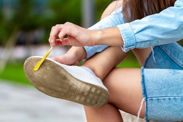 Женщина снимает жевательную резинку, прилипшую к ее обуви во время ходьбы