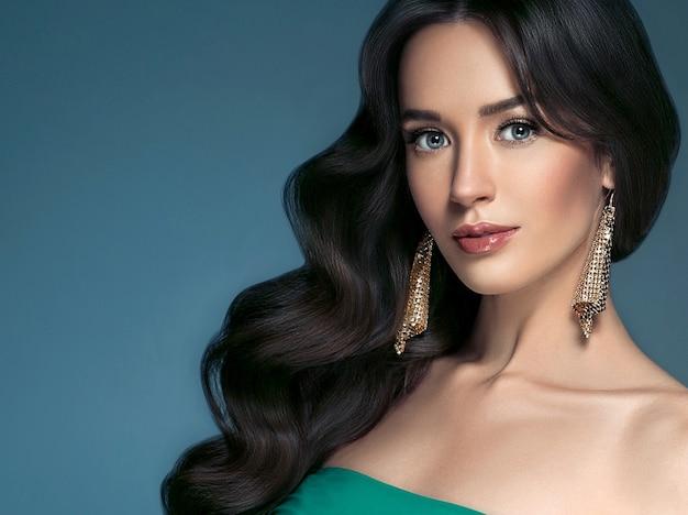 青い背景の上の女性の完璧な髪の美しい女性の肖像画。ブルネットのヘアケア長い巻き毛のヘアスタイルの美しさの概念。スタジオショット。