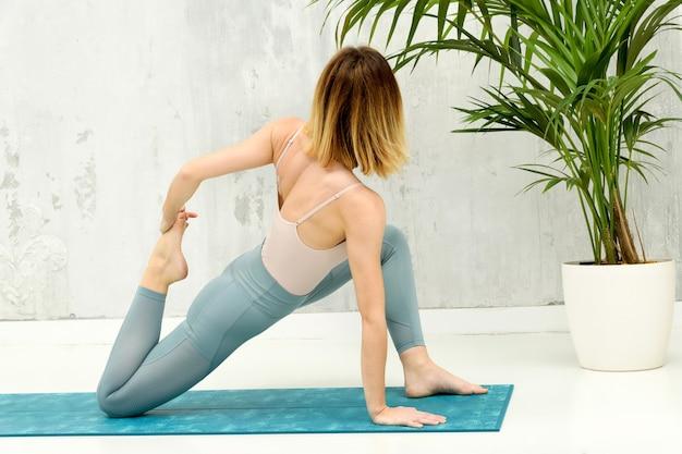 Женщина выполняет вариационную позу йоги с низким выпадом в низком угле обзора сзади, когда она поворачивается, чтобы удержать ногу