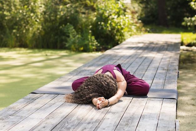 Женщина выполняет упражнение баласана, сидя на коврике в парке солнечным утром, поза ребенка