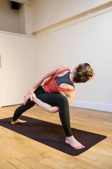 バウンド側の角度を行う女性は、運動マットの上にポーズ