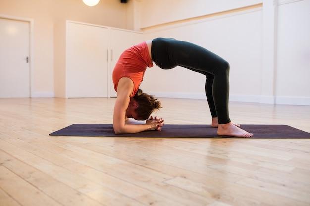 Woman performing chakrasana on exercise mat