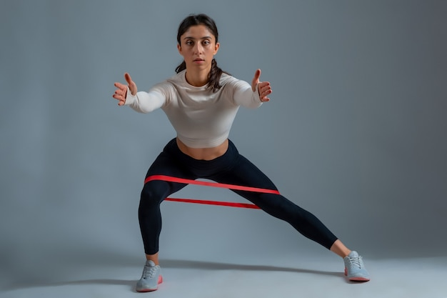 Woman performing lateral lunges with resistance band on grey wall