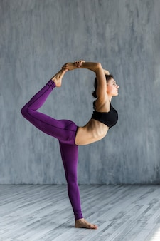 Woman performing a lord of the dance yoga pose