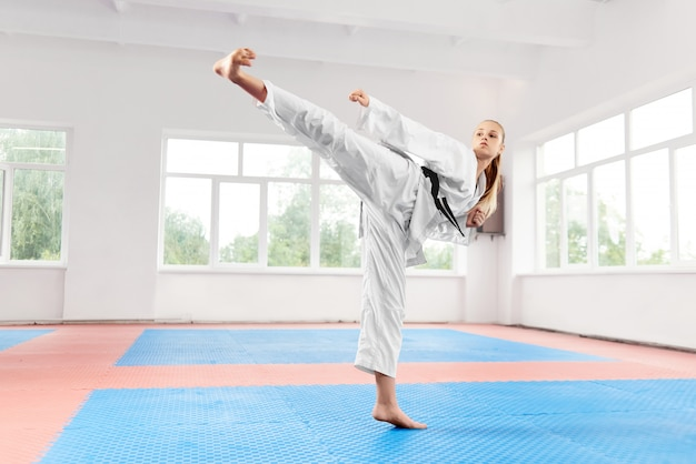 Woman performing martial arts high kick at fight class.