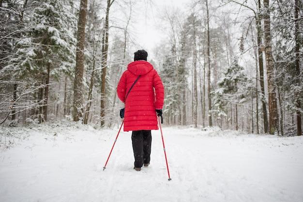 Женщина выполняет нордическую ходьбу в заснеженном зимнем лесу
