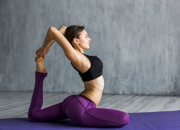 Woman performing a one-legged king pigeon pose
