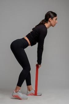 Женщина выполняет становую тягу на серой поверхности