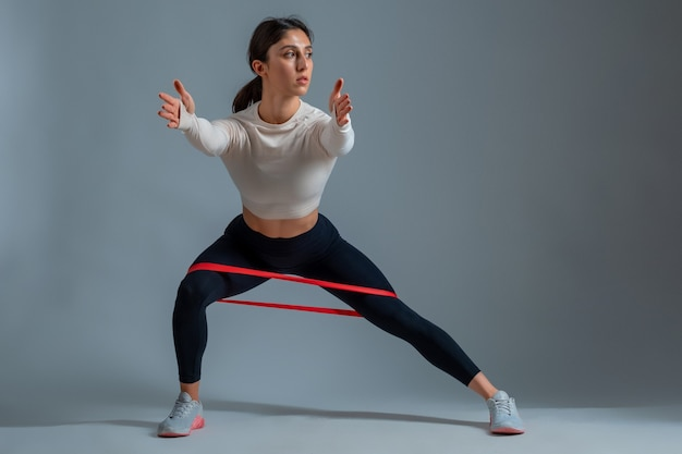 Woman performing resistance band side lunges on grey wall