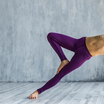 Woman performing a side angle tree pose