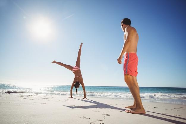 Женщина выполняет сальто на пляже