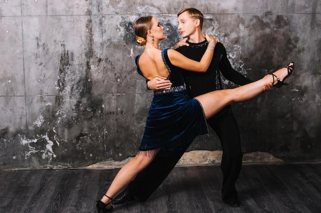 Женщина выполняет раскол во время страстного танца партнера