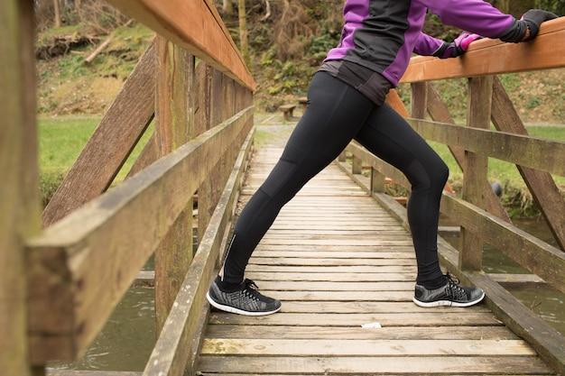 Donna che esegue esercizio di stretching sul ponte nella foresta