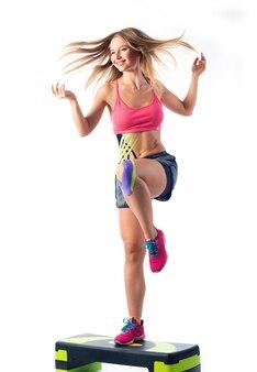 女性は草原でエクササイズを行い、キネシオテープを腹と膝にテープで貼り付けます。