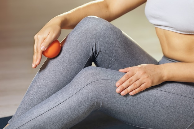 A woman performs myofascial release of the ankle muscles with a massage ball at home