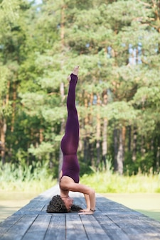 Woman performs the shirshasana exercise while standing on a mat in the park on a summer morning