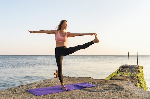A woman performs the uthita hasta padangushthasana exercise on the pier the outstretched leg pose