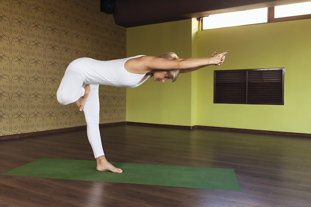 A woman performs the vrikshasana exercise a type of tree pose working out in a white jumpsuit