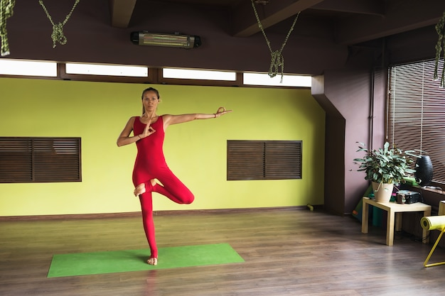 A woman performs vrikshasana exercise with a gesture of consciousness