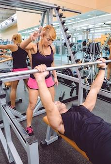 フィットネスセンターでバーベルを使ったベンチプレストレーニングで筋肉質の男性を励ます女性パーソナルトレーナー。トレーニングコンセプトの動機。