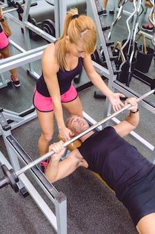 フィットネスセンターでバーベルを使って正しいベンチプレストレーニングのために男性を筋肉質にするのを助ける女性パーソナルトレーナー