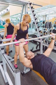 피트니스 센터에서 바벨을 들고 벤치 프레스 훈련을 하는 여성 개인 트레이너가 근육질 남자에게 소리를 지릅니다. 교육 개념의 동기 부여입니다.
