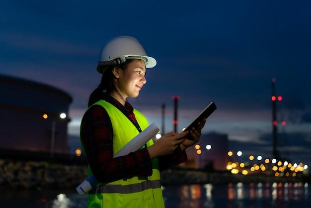 디지털 태블릿 밤에 근무하는 여성 석유 화학 엔지니어.