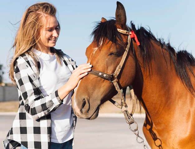 Woman petting adorable horse