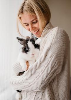 Женщина гладит очаровательный кролик