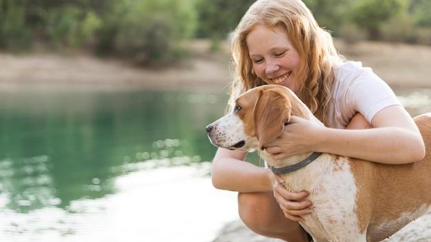 Женщина гладит свою собаку на берегу озера