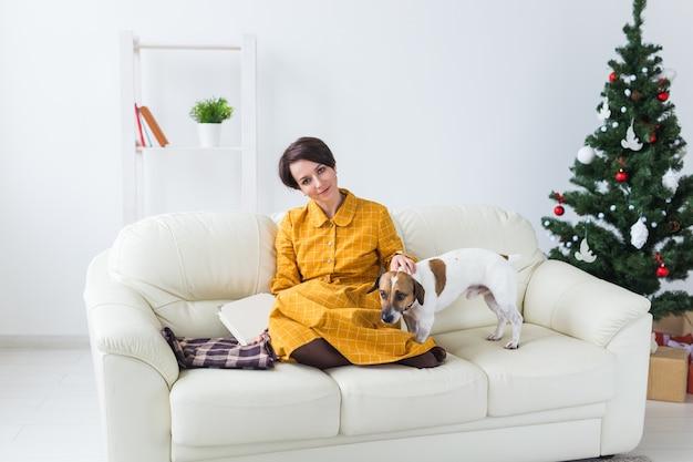 Женщина гладит собаку на диване рядом с елкой