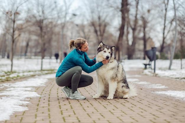 눈 덮인 겨울 날 공원에서 웅크리고 있는 동안 여자가 개를 쓰다듬어줍니다. 애완 동물, 주말 활동, 겨울, 눈, 우정