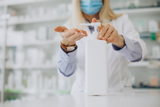 Woman pharmacist using sanitizer at pharmacy