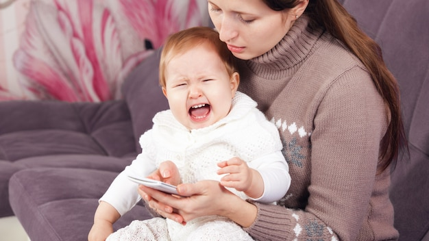 The woman on the phone, ignores the crying child. the baby is crying