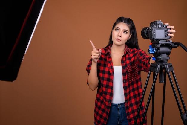 Woman photographer adjusting camera on tripod while thinking
