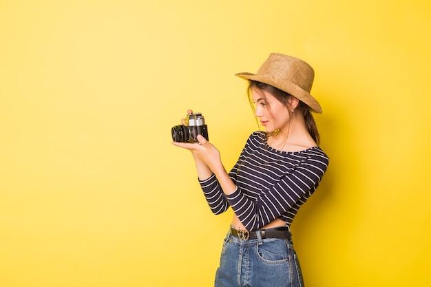 Женщина фотограф красота кавказская брюнетка молодая девушка на желтом фоне