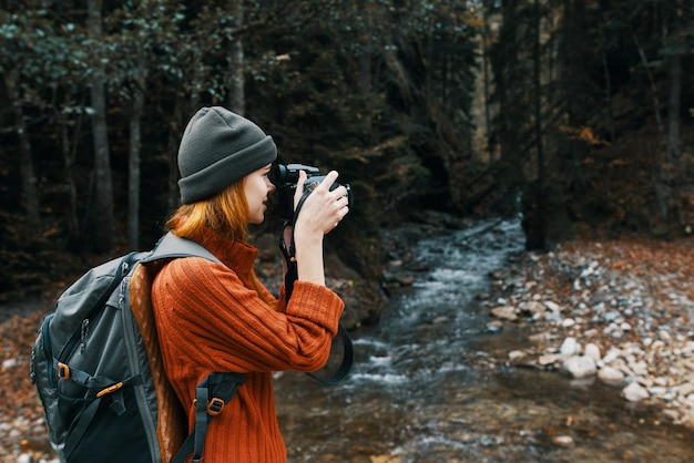 Woman photographer holding a camera in hand near the river in the mountains and forest in the