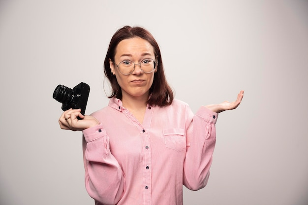 Woman photographer holding a camera on a white. high quality photo