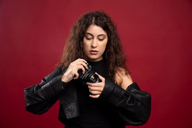 Женщина-фотограф во всем черном костюме с фотоаппаратом.