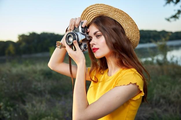 カメラのレンズを覗き込む帽子をかぶった女性写真家は、自然の趣味を笑顔にします。