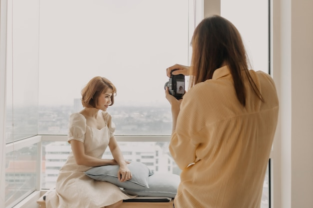 Woman photographer is taking a photo of her woman fashion model