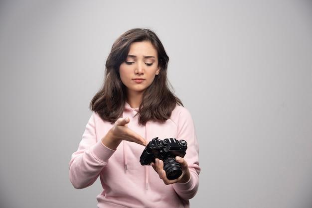 Женщина-фотограф, глядя на фотографии на камеру.