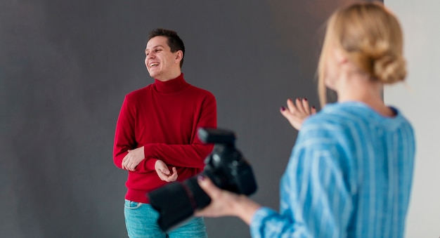 Woman photographer and male model laughing