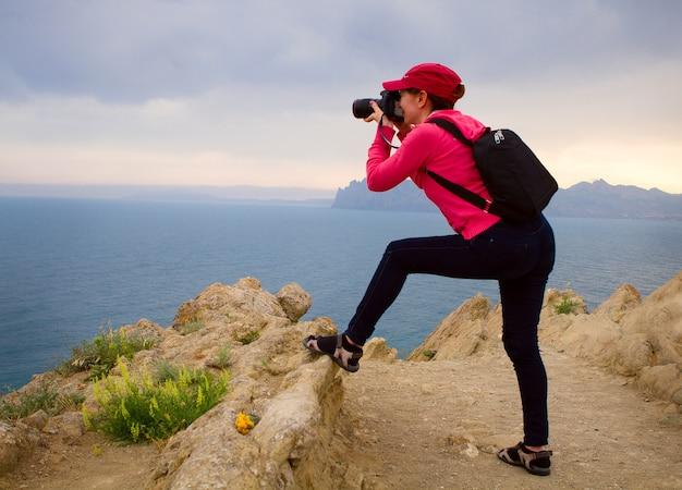 山の頂上と写真の風景を撮る女性写真家。