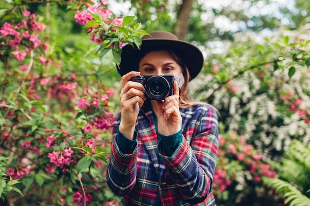 Женщина-фотограф снимая фотографии на цифровой фотоаппарат в летнем саду в защитной медицинской маске. фрилансер гуляет по парку и снимает цветущие кусты