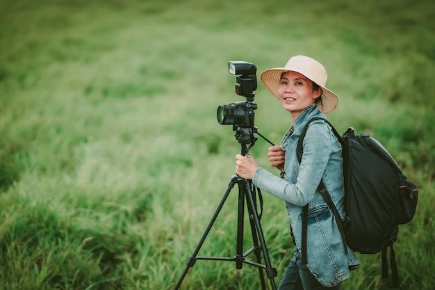 女性写真家が丘の自然で写真を撮る